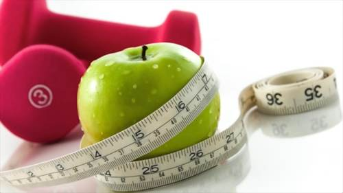 Apple wrapped in a tape measure with pink weights