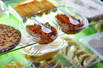 Food containers in convenience store deli shelf