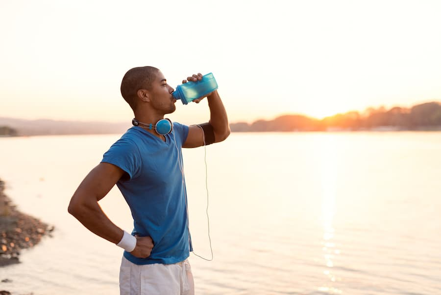 person drinking protein beverage in front of lake