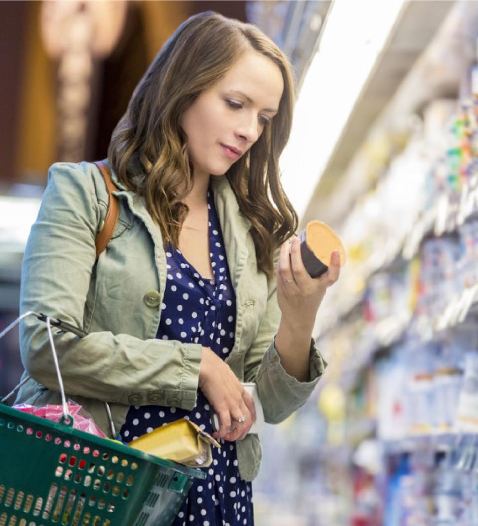 person looking at food label on package in grocery store