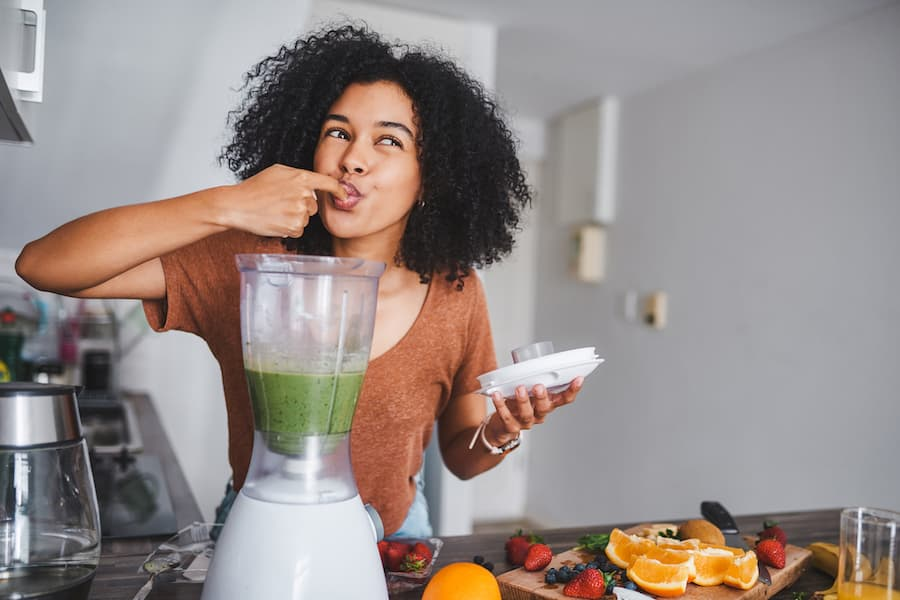 Person in a good mood tasting smoothie from blender
